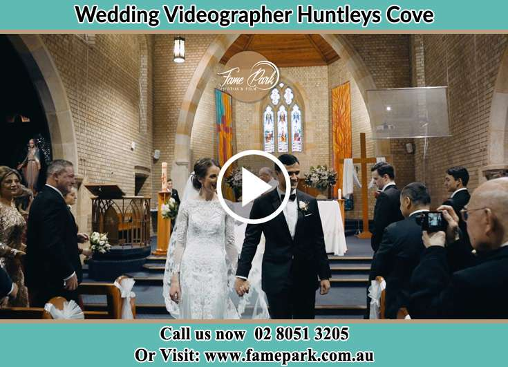 The newly weds walking through the well wishers Huntleys Cove NSW 2111
